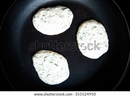 Raw pancakes with herbs on a pan. Toned. - stock photo