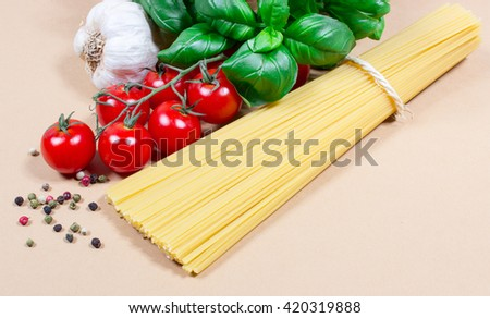 Raw pasta and ingredients for pasta with tomatoes, garlic, basil and pepper.