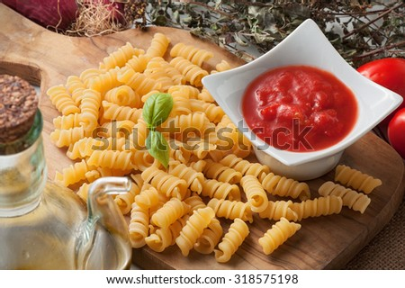 Raw pasta and ingredients (tomato sauce, basil and olive oil). - stock photo