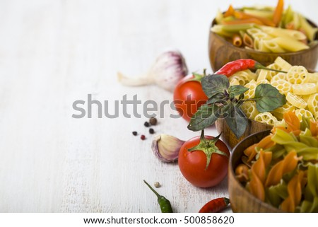 Raw pasta and spices in wooden table