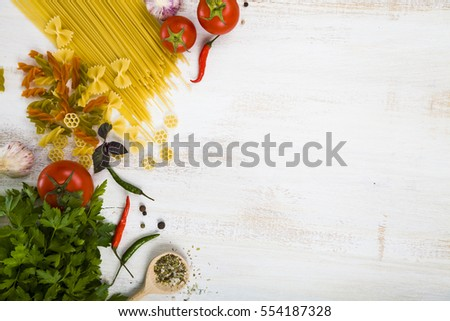 Raw pasta and spices in wooden table. Pasta and ingredients: chili, tomatoes, basil, garlic and parsley close-up.