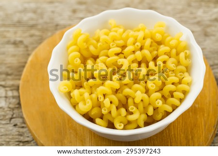 raw pasta in a white plate on cutting Board on wooden background. A healthy diet