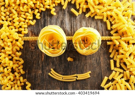 Raw pasta in shape of face - stock photo