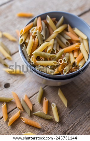 raw pasta on wood background - stock photo