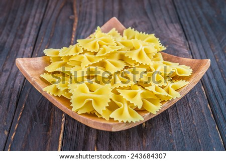 Raw pasta on wooden background - process old dark style picture