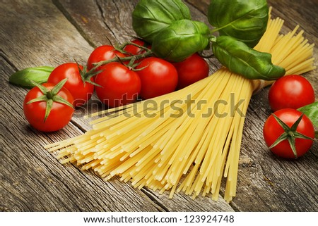 raw pasta with basil and cherry tomato - stock photo