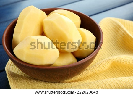 Raw peeled potatoes in bowl  on color wooden background - stock photo