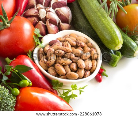 Raw pinto  beans and vegetables isolated on white