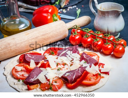 Raw pizza with parmigiano and proscuitto - stock photo