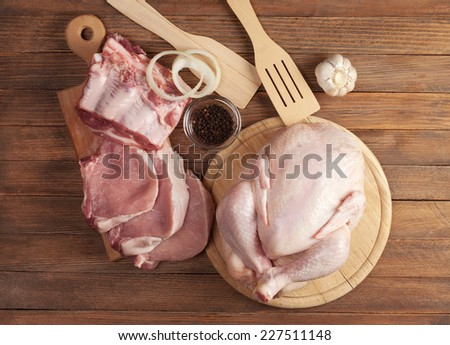 raw pork and chicken on a wooden table - stock photo