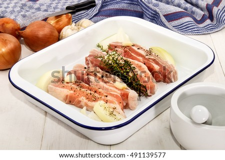raw pork belly with crushed peppercorn, garlic, onion and fresh thyme in enamel roasting tin