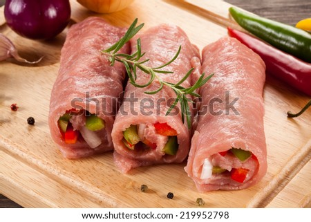 Raw pork chops on cutting board and vegetables - stock photo