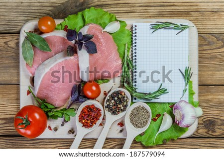 Raw pork meat and spices on rustic table with paper for recipe - stock photo