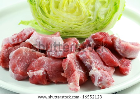 Raw pork meat with iceberg lettuce