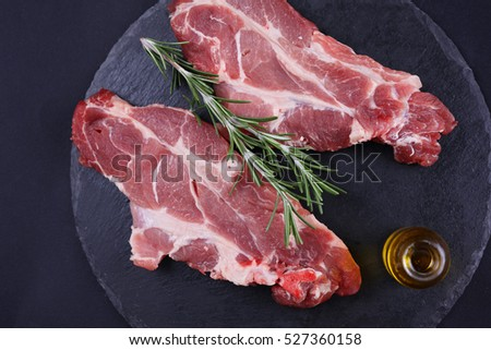 Raw pork neck meat on black background, rosemary, olive oil. Cooking background, healthy eating concept.