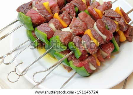 raw pork skewers on a plate - stock photo