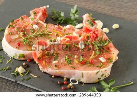 Raw pork steak on dark background with herbs - stock photo