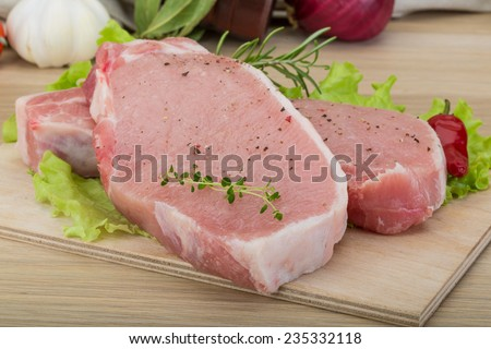 Raw pork steak - ready for cooking with herbs - stock photo