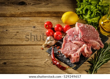 Raw pork steaks on stone board with herbs, tomatoes, garlic and lemon.