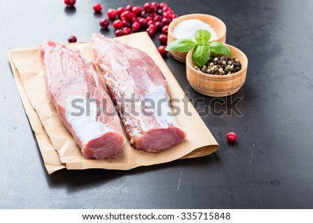 Raw pork tenderloin on craft paper ready to cook - stock photo