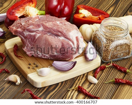 raw pork with vegetables and spices on wooden table