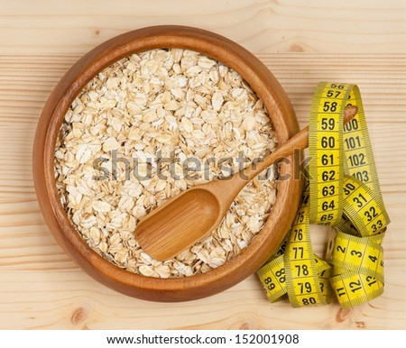Raw porridge in a bamboo bowl with tape measure over wooden background - stock photo