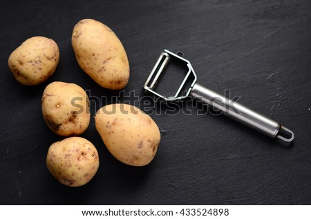 Raw potato food . Fresh potatoes and peeler. - stock photo