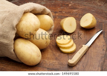 raw potatoes and knife on a wooden background - stock photo