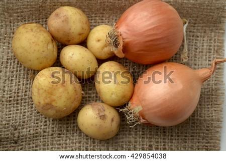 Raw potatoes and onions - stock photo