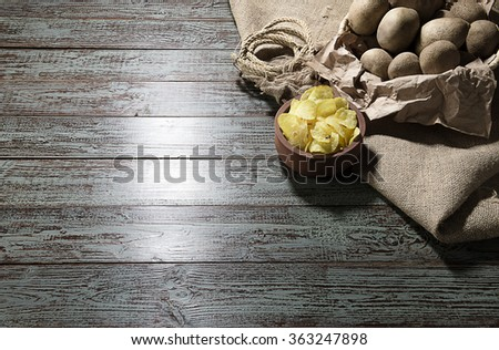 Raw potatoes and potato chips over brown wooden background. - stock photo