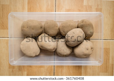 Raw potatoes in a plastic container on floor. - stock photo
