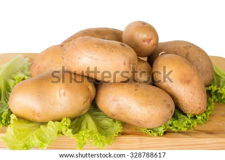 Raw potatoes lies on a chopping Board surrounded by greenery on a white background