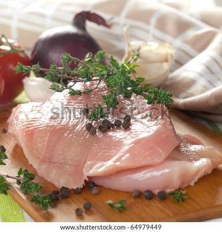 raw poultry on cutting board with pepper