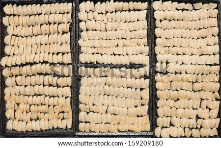 Raw prawn crackers on timber trays for sun dry processing.  - stock photo