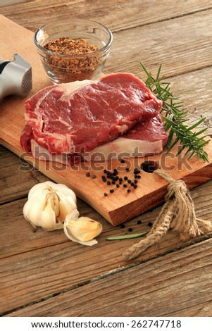 Raw prime rib beef steaks with spices, garlic and rosemary. Also available in horizontal.  - stock photo