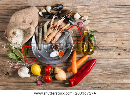 Raw products of seafood paella on a wooden table, view from above. Copy space for text. - stock photo