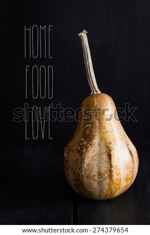 Raw Pumpkin on a Black Wooden Table. Dark Background. HOME FOOD LOVE Text Included - stock photo