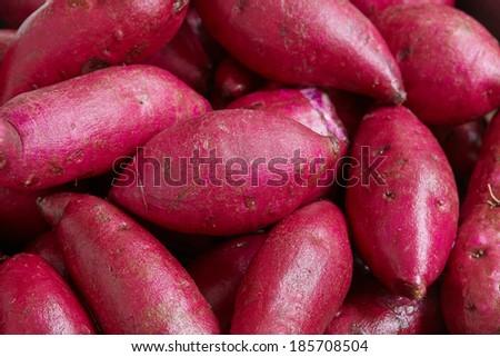Raw purple colored sweet potatoes background - stock photo