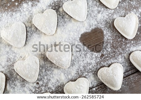 Raw ravioli in the shape of hearts, sprinkle with flour, on dark wooden table. Cooking dumplings. Top view. - stock photo