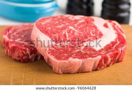 Raw red meat beef ribeye steak on wood plank - stock photo