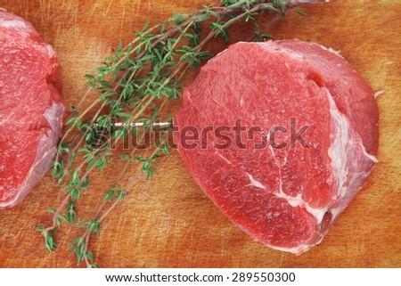 raw red meat : two fresh beef fillet chops with small thyme twig on wooden plate . isolated over white background - stock photo