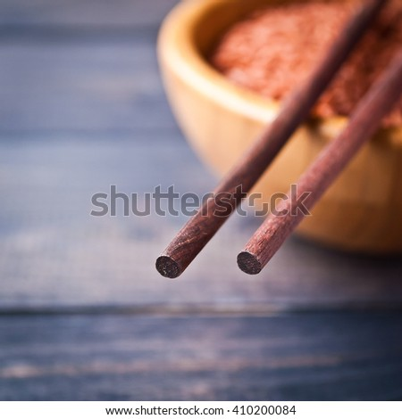 Raw red rice in bowl and wooden chopsticks. Selective focus - stock photo