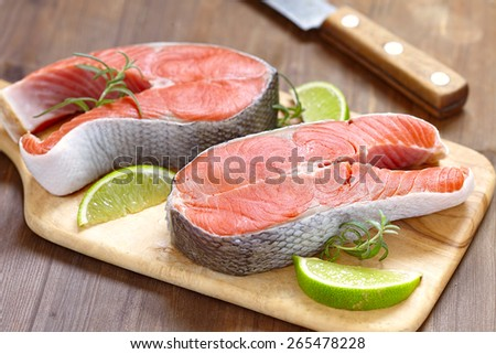Raw red salmon steaks on a cutting board - stock photo