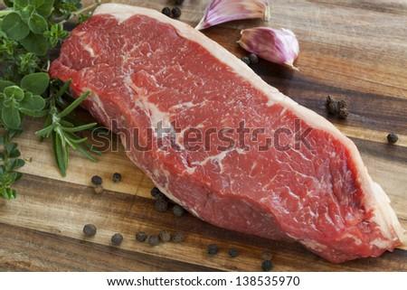 Raw red sirloin steak with fresh herbs, garlic and peppercorns. - stock photo