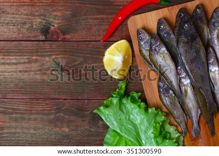 raw redfish ruff fish on the kitchen table with vegetables and lemon - stock photo