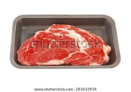 Raw rib eye steak in a polystyrene carton isolated against white - stock photo