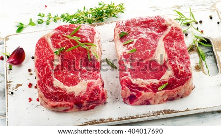 Raw rib eye Steaks  on  a wooden cutting board. Selective focus - stock photo