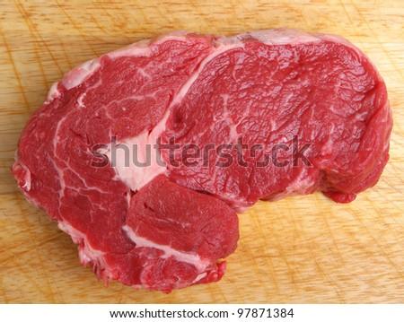 Raw ribeye beef steak on wooden chopping board. - stock photo