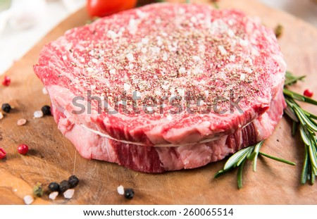 Raw Ribeye Steak Rubbed with Salt and Paper before Grilling   - stock photo