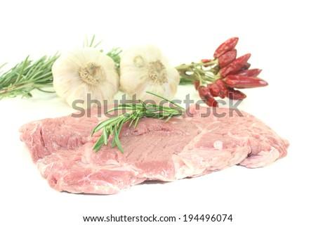 raw ribeye steak with garlic and rosemary - stock photo
